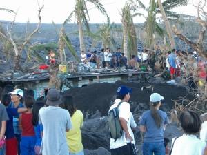 台風レミン、土石流で埋もれた民家の救出作業を見守る人々