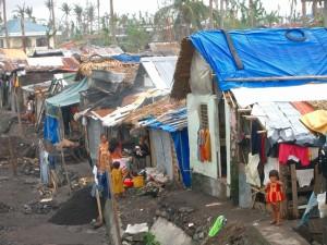 台風レミン、風で屋根を飛ばされテント生地で屋根を覆うスコーター(スラム街)の家